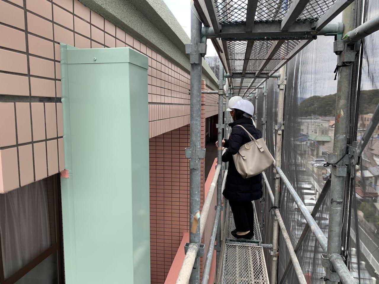 足場に登って建物の工事状況を確認しています